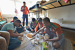 While Mohammed Adnan talks with his mother via Skype in the background, his fellow travelers from Pakistan eat a shared meal in a government-run refugee center in Vamosszabadi, Hungary. Hungarian Interchurch Aid, a member of the ACT Alliance, provides child care and other services to residents in the center, who come from Syria, Iraq and other countries and are bound for western Europe.