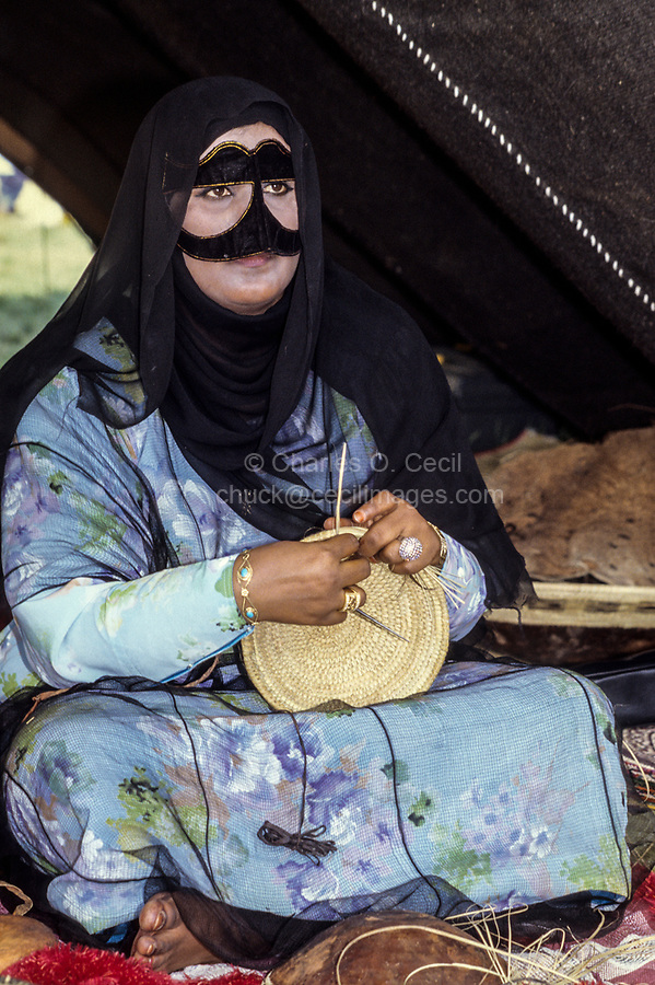 Oman.  Woman with Burqa Making Basket for Camel's Milk.