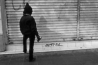A Chilean student seen before spraying a political slogan on the roller shutter during the anti-government protest in Valparaíso, Chile, 21 May 2002.