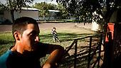 Garden City, Kansas, USA, August 2011:.Afternoon at the trailer park. Many hispanic immigrants from Mexico and Salvador live in the trailers. Most of them came here to work at Tyson meatpacking plant, which slaughters and processes 6 thousand cattle a day. Kansas dominates American beef industry, by producing one quarter of all beef in the USA, while being heavily dependent on cheap immigrant labour..(Photo by Piotr Malecki / Napo Images)..Garden City, Kansas, Stany Zjednoczone, Sierpien 2011:.Popoludnie na osiedlu przyczep samochodowych, znajdujacym sie obok parkingu ciezarowek wozacych bydlo. Duzo emigrantow z Meksyku i Salwadoru mieszka w przyczepach samochodowych, a pracuje w zakladach miesnych Tyson, ktore zabijaja i przerabiaja 6 tysiecy sztuk bydla dziennie. Stan Kansas zdominowal rynek wolowiny w Stanach Zjednoczonych, produkujac jedna czwarta calej amerykanskiej wolowiny. Amerykanski przemysl miesny jest bardzo uzalezniony od taniej sily roboczej, ktora daja emigranci..Fot: Piotr Malecki / Napo Images.