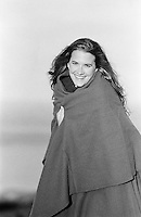 Woman smiling outdoors in a blanket