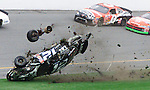 """Ryan Newman's #12 Alltel Dodge disintegrates as he crashes near the start-finish line during running of the Daytona 500 at the Daytona International Speedway in Daytona Beach, Florida February 16, 2003. Forty three drivers are competing in the 45th running of the """"Great American Race."""" Jack Sprague's #0 NetZero Pontiac passes above along with the #19 Dodge Dealers Dodge driven by Jeremy Mayfield."""