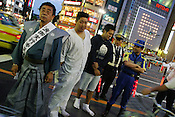 Men in the street stand on the periphery of a local festival,  Ueno, Tokyo, Japan.