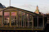 New Caledonia Glasshouse (formerly The Mexican Hothouse) built in the 1830s by Charles Rohault de Fleury, Jardin des Plantes, Museum National d'Histoire Naturelle, Paris, France. View from the side showing the glass and metal rooftop cupola in the early morning light. In the background is the minaret of the Grande Mosquee de Paris (Great Mosque of Paris). The New Caledonia Glasshouse, or Hothouse, was the first French glass and iron building.