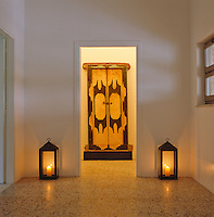 A pair of lanterns stand on either side of an Indonesian carved door