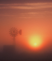 Fine art western landscape of orange and yellow sunrise in tule fog, shrouding a windmill and outbuilding, with whisps of cloud framing the top of the image, evocative of ranch sunrises in Oklahoma and other ranch locations.
