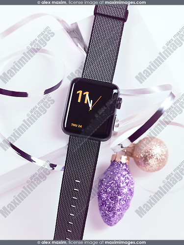 Apple Watch smartwatch with a gift wrapped box and Christmas ornaments, Christmas present still life