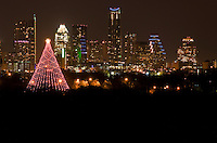 The Zilker Christmas Tree Stands 155 feet tall and is composed of 39 streamers, each holding 81 multicolored, 25 watt bulbs, totaling 3,309 lights. At the top of the tree, a double star measures 10 feet from point to point. The double star displays 150 frosted bulbs. This unique spiral pattern of lights was created by City of Austin electricians. At its circumference, the tree measures 380 feet. The diameter is 120 feet. The base of the tree is made up of 19 utility poles, each 14 feet tall, arranged in a circle around the Moonlight Tower.