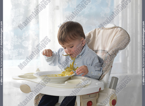 One and a half year old boy sitting in a high chair and eating soup with a spoon, spilling it on his shirt