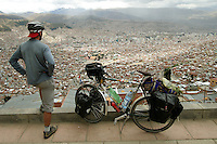 A long distance cyclist checks out the view of La Paz from El Alto, the highest capital city in the world - Bolivia - South America