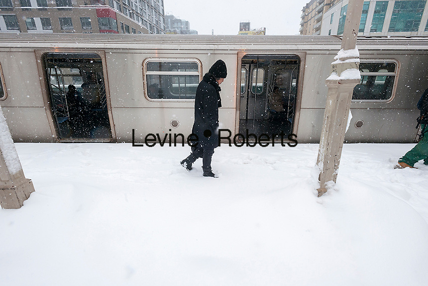 Intrepid travelers maneuver through the snow at the Queensboro Plaza station in New York during the city's first major winter storm of the season on Thursday, February 9, 2017. Meteorologists are forecasting between 8 and 14 inches of snow in the New York City region. The Metropolitan Transportation Authority has had no major delays and the trains continue to run.  (© Richard B. Levine)