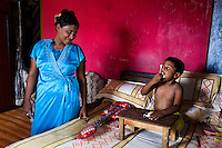 Razia Shabnam (in blue) feeds her son as he watches cartoons at home in Ekbalpore, Calcutta, West Bengal, India. Razia Shabnam, 28, was one of the first women boxers in Kolkata. She was also the first woman in her community to go to college. She is now a coach and one of only three international female boxing referees in India.  Photo by Suzanne Lee for Panos London