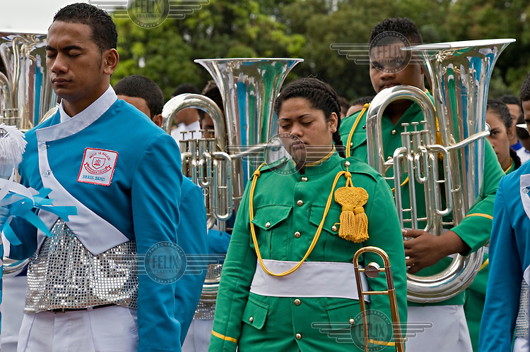 The combined schools' brass band bow their heads in prayer before they perform at the Education and Cultural Day on the first day of official celebrations marking the coronation of King George Tupou V.