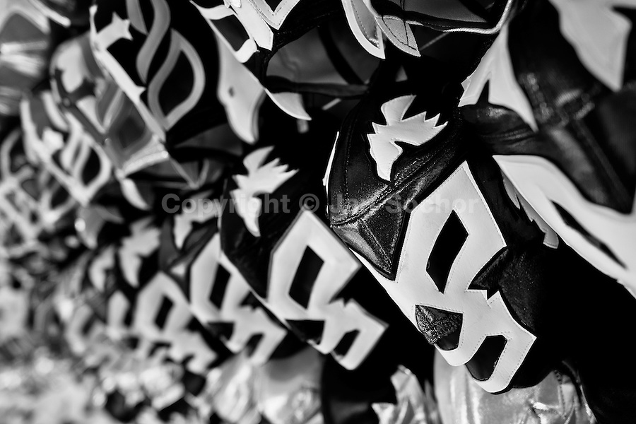 """Lucha libre wrestling masks, inspired by those worn by professional wrestlers, displayed for sale in a street shop in Mexico City, Mexico, 29 May 2011. Lucha libre, literally """"free fight"""" in Spanish, is a unique Mexican sporting event and cultural phenomenon. Based on aerial acrobatics, rapid holds and the use of mysterious masks, Lucha libre features the wrestlers as fictional characters (Good vs. Evil). Women wrestlers, known as luchadoras, often wear bright shiny leotards, black pantyhose or other provocative costumes. Given the popularity of Lucha libre in Mexico, many wrestlers have reached the cult status, showing up in movies or TV shows. However, almost all female fighters are amateur part-time wrestlers or housewives. Passing through the dirty remote areas in the peripheries, listening to the obscene screams from the mainly male audience, these no-name luchadoras fight straight on the street and charge about 10 US dollars for a show. Still, most of the young luchadoras train hard and wrestle virtually anywhere dreaming to escape from the poverty and to become a star worshipped by the modern Mexican society."""