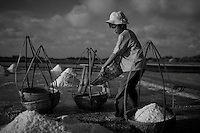 Salt people of Vietnam..Duong Tran, 12, fills baskets with salt so his aunt can carry them to a dry location...Farmers harvest salt cultivated in rice-patty like fields in Ben Tre, a village in southern Vietnam. The salt season usually begins in January and ends in March as these are the driest months. Photo taken Friday, March 21, 2008. Kevin German / kevin@kevingerman.com