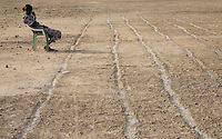 A spectator waits by the 100m track at the Twic Olympics in Wunrok, Southern Sudan.