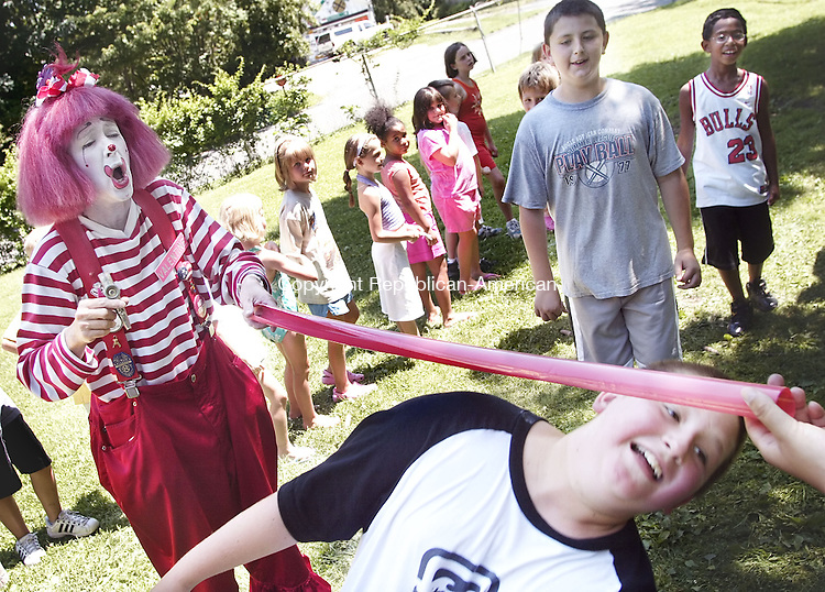 PLYMOUTH, CT-- 31 July 2007--073107TJ05- Valentine the Clown, left, reacts as Sean Wollenberg, 11, limbos under the bar and Ariel Batista, 9, and Eric Orr, 12, from right, all from Plymouth, Conn., watch during a Terryville Park and Recreation summer program at Veterans Memorial Playground in Plymouth, Conn., on Tuesday, July 31, 2007.<br />T.J. Kirkpatrick / Republican-American