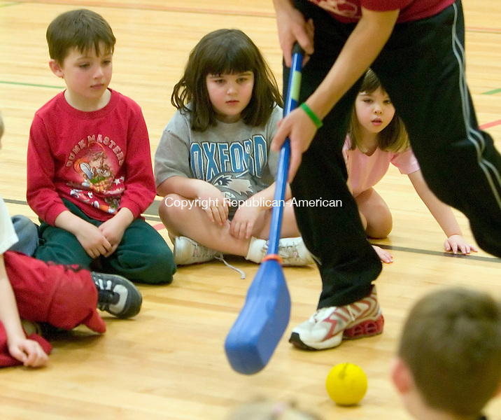 OXFORD, CT- 20 FEB 06- 022007JT03- <br /> Marc Bedient, 6, Katelyn Capodagli, 6, and her sister Kristy, 5, watch camp director Tony Nocera demonstrate how to play hockey during a sports camp offered by the Parks and Recreation Department at Great Oak School in Oxford on Tuesday.<br /> Josalee Thrift Republican-American