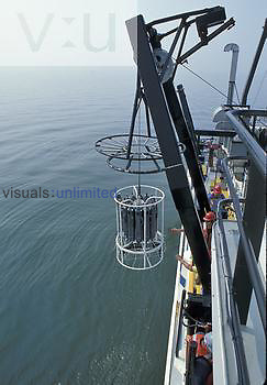 Deploying a Rosette Sampler from a research ship to measure biochemical and other data from water samples.