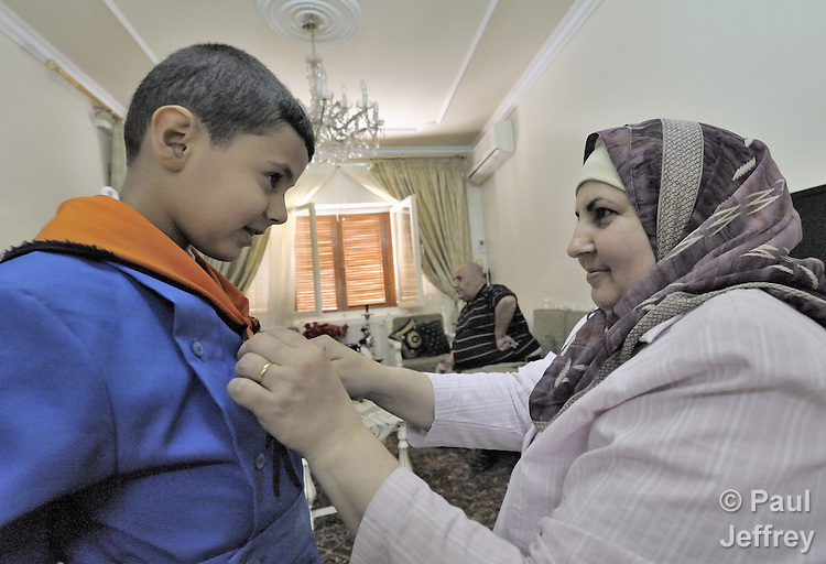 Sawsan Hussin, an Iraqi pharmacist living as a refugee in Damascus, Syria, helps her son Yousif, 7, get ready for school. More than one million Iraqi refugees are estimated to live in Syria, part of a large diaspora of families who fled the violence of the U.S. occupation.