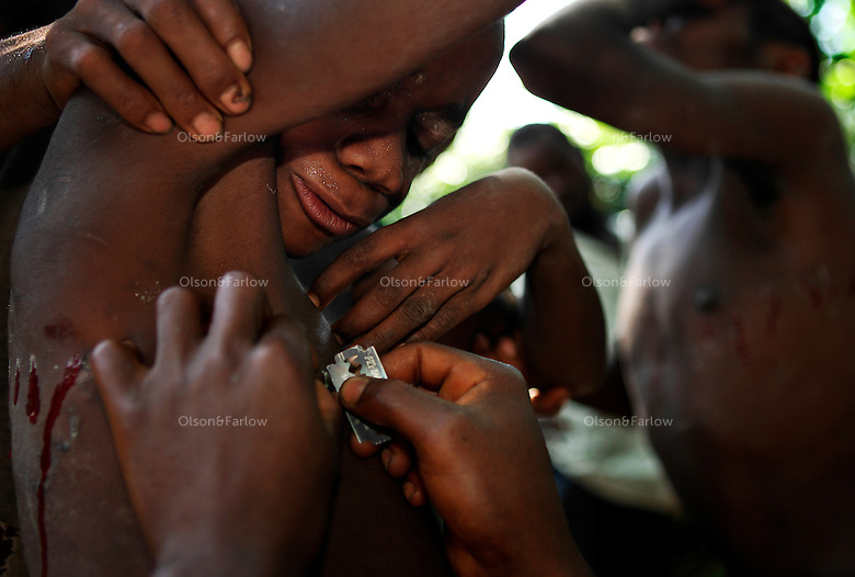 Ritual Scarification with Razor Blade..Two razor blades are pulled out to use on all the boys.  The cuts are marked with paint and then the boys are cut as two other Bantus hold them back.  Then the chief rubs a black tar into the wounds to make sure they will scar.