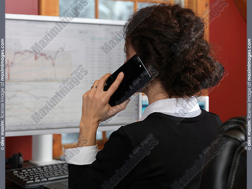 Woman stock trader speaking on the phone Apple iPhone 7 plus with stock charts displayed on her computer monitor
