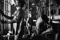 India. Province of Gujarat. Alang. Workers, all men, cut metal tubes in the engine room of a merchant ship. Alang, located in the Gulf of Khambhat, is a ships breaking place and is considered as the biggest scrapyard in the world. Ships recycling for its metals. Environmental issues. Hazardous waste. © 1992 Didier Ruef