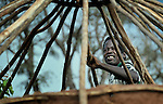 Displaced by war, a man puts a roof on his hut in the Makpandu refugee camp in Southern Sudan, 44 km north of Yambio, where more that 4,000 people took refuge in late 2008 when the Lord's Resistance Army attacked their communities inside the Democratic Republic of the Congo. Attacks by the LRA inside Southern Sudan and in the neighboring DRC and Central African Republic have displaced tens of thousands of people, and many worry the attacks will increase as the government in Khartoum uses the LRA to destabilize Southern Sudan, where people are scheduled to vote on independence in January 2011. Catholic pastoral workers have accompanied the people of this camp from the beginning.