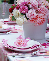 The place settings are decorated with roses on this pretty table set for an al fresco summer lunch