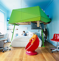 A boy lies on a futuristic bed designed by Ab Rogers watching television in his brightly coloured bedroom