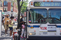 Commuters board an M102 bus in in Harlem in New York on Sunday, June 23, 2013. (© Richard B. Levine)