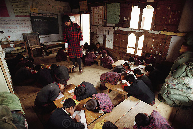 English lesson in classroom at the school in Gaselo, Bhutan. Nalim's daughter Bangam is in attendance (although out of frame). Children in Bangam's class range from 6 to 17 in age. The school is an hour's walk from Shingkhey Village. Bhutan. From Peter Menzel's Material World Project.