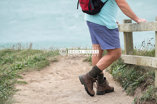 A walker takes a rest on the South West Coastal Path in Cornwall.