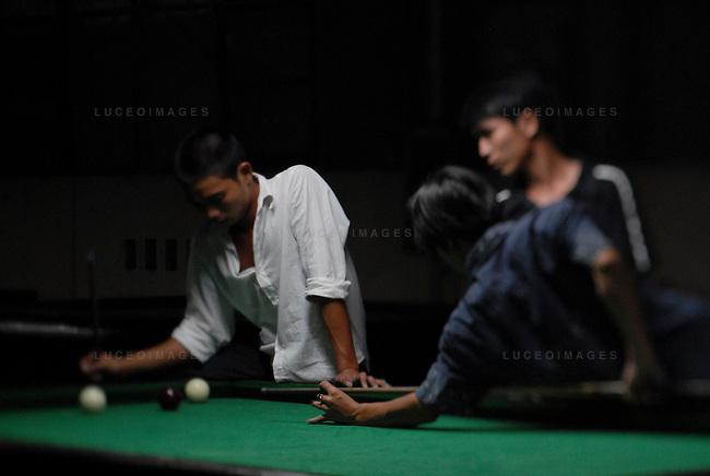 Vietnamese men play billiards in Hoi An, Vietnam.