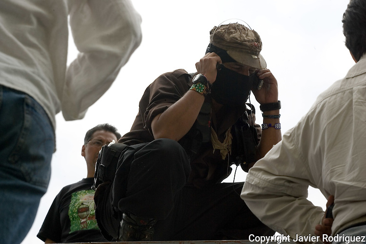 Zapatista rebel leader Subcomandante Marcos, the Delegado Zero, talks by cellphone as he updates information about San Salvador Atenco clashes during a rally at the Plaza de las 3 Culturas main square in Tlatelolco, May 3, 2006. Subcomandante Marcos addressed a speech before hundreds of people and declared a red alert after the San Salvador Atenco peasants clashed with police in Texcoco city, in Mexico State. More than 90 people were arrested during the clashes. Photo by Javier Rodriguez
