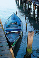 A small blue-painted boat is tied up to one of the rough wooden jetties that make up the fishing port of Carrasqueira