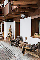 The chalet's decked terrace is furnished with sun loungers covered with inviting fur rugs