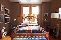 In the master bedroom the bed has been positioned in front of the shuttered window and dressed with a Union Jack flag quilt by textile artist Becky Oldfield