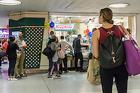 """Customers clamor around the Krispy Kreme in Penn Station in New York for a free donut celebrating National Donut Day  on Friday, June 3, 2016. National Donut Day, the first Friday in June, was created in 1938 by the Salvation Army to honor the """"donut lassies"""" who administered treats and solace to soldiers during WW1. (©  Richard B. Levine)"""