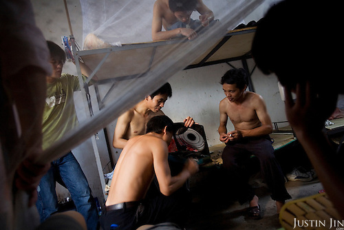 """Jeans workers fix a fan in their dormatory in Zhongshan city, China. .This picture is part of a photo and text story on blue jeans production in China by Justin Jin. .China, the """"factory of the world"""", is now also the major producer for blue jeans. To meet production demand, thousands of workers sweat through the night scrubbing, spraying and tearing trousers to create their rugged look. .At dawn, workers bundle the garment off to another factory for packaging and shipping around the world..The workers are among the 200 million migrant labourers criss-crossing China.looking for a better life, at the same time building their country into a.mighty industrial power."""
