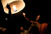 people look on as a buddhist monk lets go of a paper balloon in Seam Reap, Cambodia.