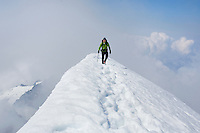 &quot;WALKING THE RIDGE&quot; -- A mountaineer walks along the knife edge summit ridge of El Dorado Peak in Washington's North Cascades National Park. Summer.