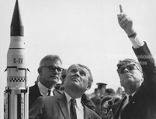 Marshall Space Flight Center (MSFC) Director, Doctor Wernher von Braun explains the Saturn Launch System to United States President John F. Kennedy at Cape Canaveral, Florida on November 16, 1963. National Aeronautics and Space Administration (NASA) Deputy Administrator Robert Seamans is to the left of von Braun..Credit: NASA via CNP