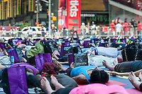 "Thousands of yoga practitioners pack Times Square in New York to participate in a mid-day Bikram Yoga class on the first day of summer, Friday, June 21, 2013. The 11th annual Solstice in Times Square, ""Mind Over Madness"",  stretches the yogis' ability to block out the noise and the visual clutter that surround them in the Crossroads of the World"". (© Richard B. Levine)"