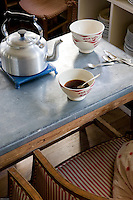 In the kitchen antique red-and-white striped armchairs next to a zinc-topped table is the setting for an informal cup of morning coffee