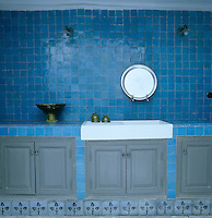 Tiles are the most practical and beautiful solution in any kitchen; the blue ones that cover the walls in this example are matched with matt grey painted cupboards