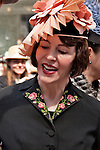 A woman wearing a black suit and a pink fan hat in the New York City Easter Parade