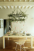 A large candelabra covered in olive branches and pink and white Christmas decorations hangs over a table laid for afternoon tea