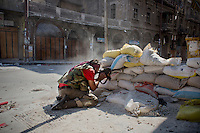 A rebel Free Syrian Army (FSA) fighter fires on a Syrian Army position 200m down an alley in the old city area of Aleppo.