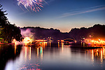 Boats jockey and fireworks come from all directions just at sunset on the 4th of July at Lake Thoreau, Reston, Virginia, USA.  An evening flotilla forms every 4th of July to enjoy the impromptu fireworks displays put on by residents and boat owners at Lake Thoreau in Reston, Virginia, USA.  This is an HDR built from a series of nine time exposures as fireworks were being shot from multiple points around the lake.